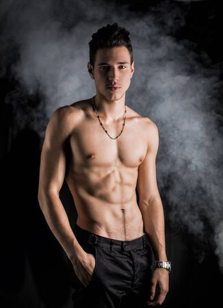 Lean athletic shirtless young man standing on dark background, with smoke around him photo