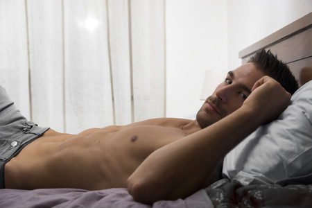 shirtless man: Shirtless male model lying alone on his bed