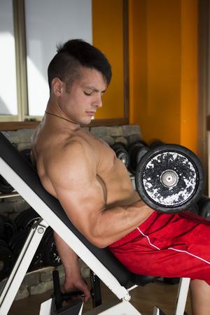 man working out: Hombre joven apto descamisado muscular que se resuelve con pesas en un gimnasio