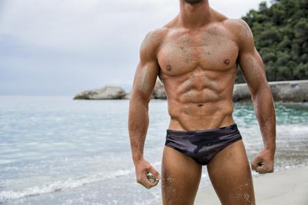 cuerpo hombre: Hombre fuerte ajuste muscular que presenta en traje de ba�o en una playa tropical