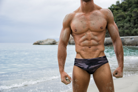 Strong muscular fit man posing in a swimsuit on a tropical beach photo
