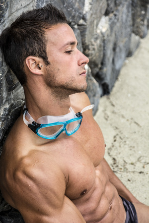 Handsome muscular fit young man relaxing at the beach sitting on the sand leaning against a wall with his swimming goggles around his neck, closeup portrait in profile photo