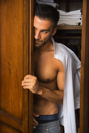 handsome young man standing shirtless with a shirt draped over his shoulder peering out of a walk in closet with a smile