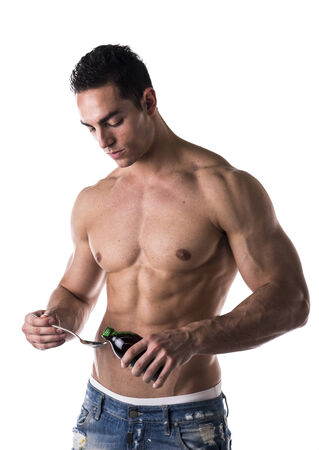 Strong muscular man taking medication or liquid diet supplements and vitamins standing bare chested carefully measuring a dose in a spoon isolated on white photo
