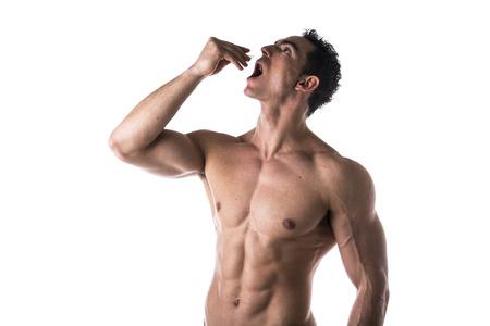descamisados: Muscular hombre fuerte de tomar suplementos de dieta o medicaci�n farmac�utica de pie sin camisa con la boca abierta y la cabeza echada hacia atr�s como se le cae una p�ldora de su mano o pone algo en la boca Foto de archivo