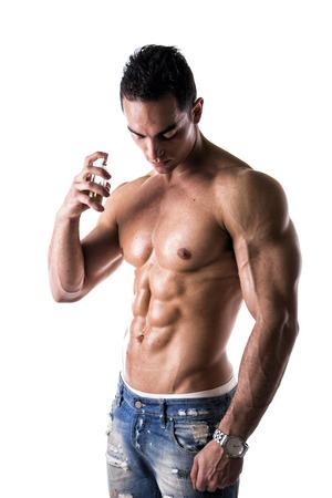 fragranza: A petto nudo maschile modello di spruzzare acqua di colonia su sfondo bianco Archivio Fotografico