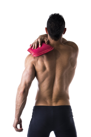 Back of muscular young man with shoulder pain, holding hot water bottle, isolated on white photo