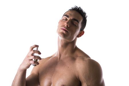 smell: Modelo masculino descamisado pulverizaci�n colonia en el fondo blanco, los ojos cerrados Foto de archivo