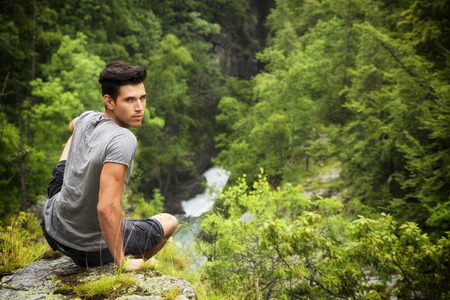 Handsome muscular young man sitting in lush green mountain scenery looking at camera photo