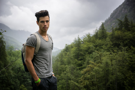 Handsome muscular young man backpacking or hiking in lush green mountain scenery looking at camera Standard-Bild