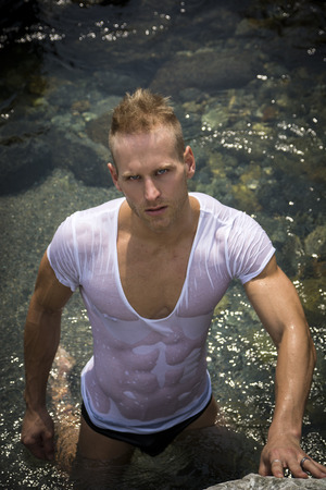 Attractive young bodybuilder by the sea with wet t-shirt on, serious expression