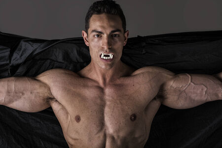 Naked muscular fit young man posing as a vampire or Dracula in a black cloak showing off his powerful body bearing his fangs with arms spread open photo