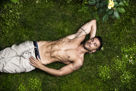 Good looking, shirtless fit male model relaxing lying on the grass, shot from above