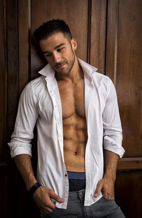 puertas abiertas: Apuesto joven atractiva que se coloca en camisa blanca abierta con una sonrisa delante de las puertas del armario de madera Foto de archivo