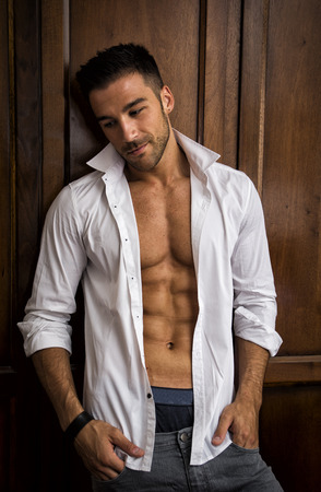 closet: Sexy handsome young man standing in white open shirt with a smile in front of wood closet doors
