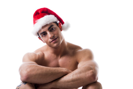 Attractive young muscle man sitting and smiling with muscular ripped body in Santa Clauss red hat