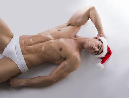 atletisch: Aantrekkelijke jonge spier man tot op de vloer met gespierde geripte lichaam in de rode hoed van de Kerstman Stockfoto