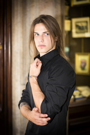 Handsome long hair young man in front of shop window wearing elegant black shirt