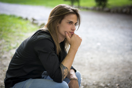 long depression: Handsome long hair young man portrait, sitting outdoor thinking, sad or worried Stock Photo