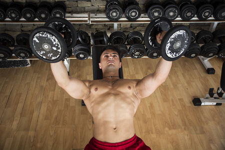 Portrait of a handsome muscular young man lifting weights on a bench at the gym photo