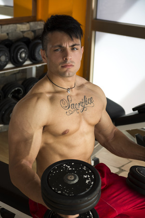 Portrait of a handsome muscular young man lifting weights at the gym, sitting on bench photo