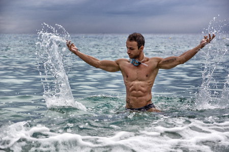 Handsome, hot young bodybuilder in the sea, splashing water up, showing his muscular torso and arms photo