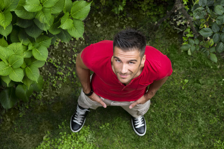 Good looking, fit male model looking up with smile, outdoors on grassland, shot from above photo