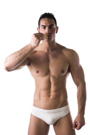 Muscular man in his underwear removing tape from his mouth on white background Stock Photo
