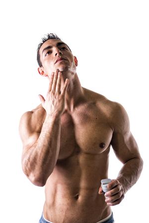 fit on: El hombre con el pecho musculoso y los abdominales que aplican la crema de afeitar en la cara en el fondo blanco