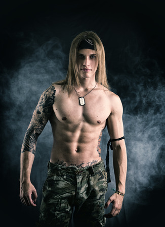 Shirtless male model wearing a bandanna smiling on smoky background