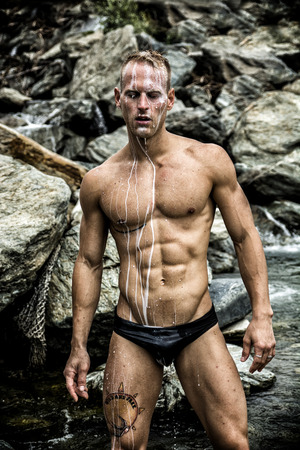 wet suit: Hot Muscular Wet Man Wearing Tiny Black Underwear with Rocky Background