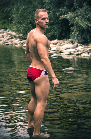 Man wearing trunks standing in shallow water looking over his shoulder Stock Photo