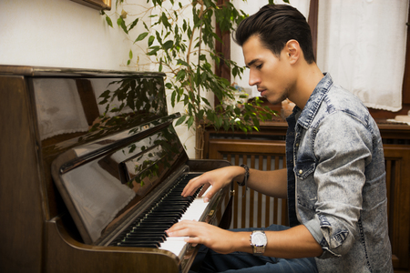 Jeune artiste beau mâle jouant son piano droit classique en bois, portrait intérieur