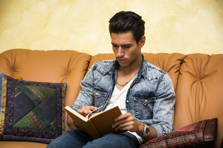 Handsome black hair young man reading book at home, sitting on couch photo