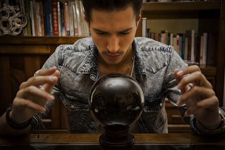 soothsayer: Handsome young man predicting the future by looking into crystal ball