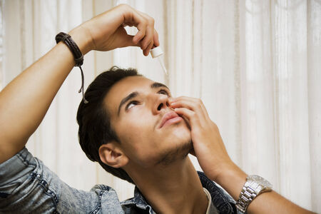 sore eye: Handsome young man dropping medicine in his eye with eye-dropper Stock Photo