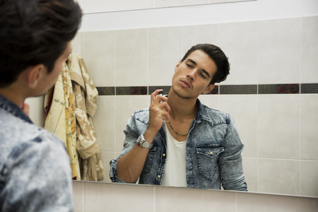 man in jeans: Handsome young man in his home bathroom, spraying cologne or perfume on neck