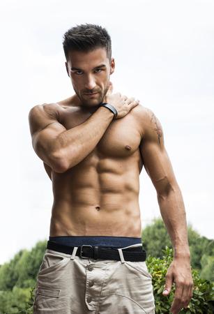 Handsome muskulösen jungen Mann mit nacktem Oberkörper im Freien, in dem Kamera Standard-Bild - 31651632