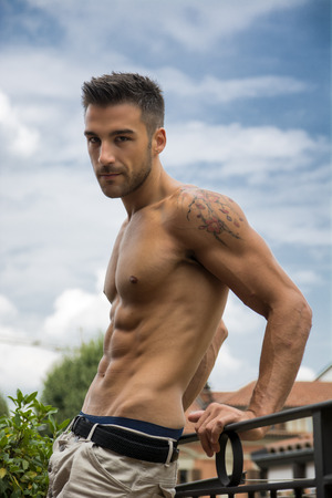 Handsome shirtless muscular young man outdoor, looking at camera photo