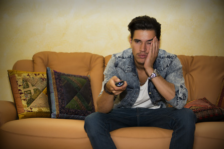 Young man sitting watching television changing the channel with the remote control with a bored expression Archivio Fotografico