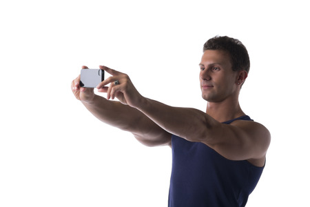 Handsome young man taking a selfie on his mobile phone holding it at arms length as he smiles at the camera, on white photo