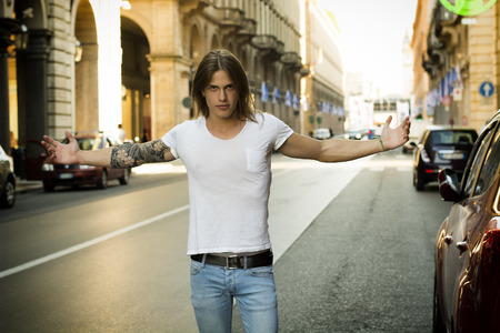 Man Wearing White T Shirt with Open Arms Standing in Street and Facing Camera