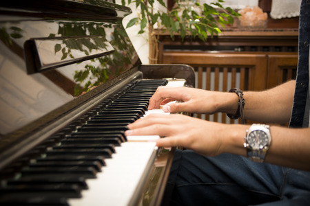 upright piano: Male hands playing piano indoors inside house