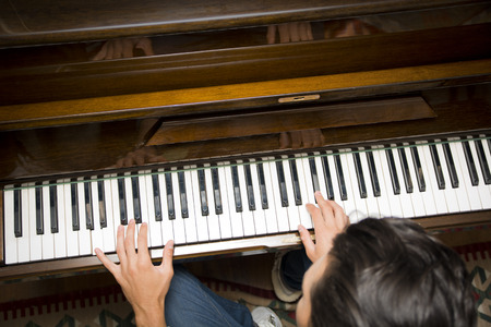 Male hands playing piano indoors inside house, shot from above photo