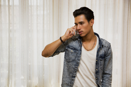 Handsome young man talking on telephone at home, looking to a side photo