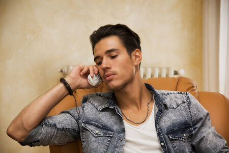 Handsome young man talking on telephone at home sitting on armchair photo