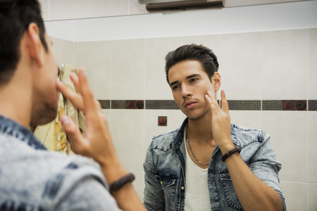 Handsome young man applying moisturizing cream on face in front of home bathroom mirror Stock Photo