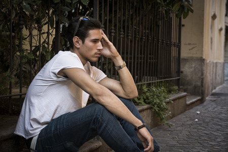 Sad, unhappy young man outdoor, sitting on pavement, holding head with his hand photo