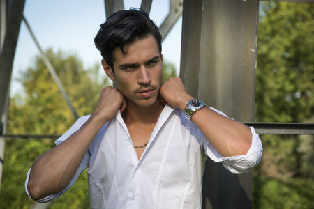 Handsome young man leaning against metal electricity trellis, looking away photo