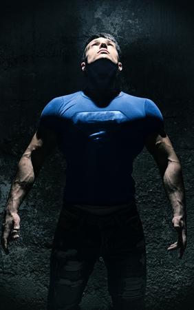 Muscle Man Looking Up Into Bright Overhead Light Illuminating Him Like a Superhero